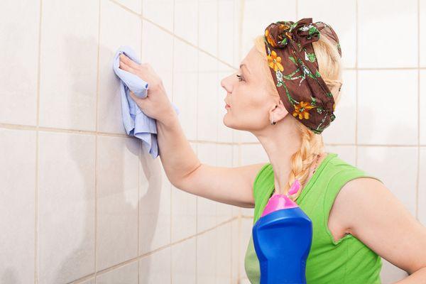 женщина чистит плитку